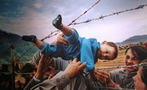Refugees passing a child across barbed wire